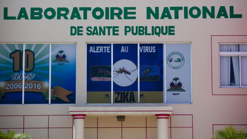 In this Thursday, May 19, 2016 photo, an alert against the spread of Zika is displayed in the window above entrance at the National Laboratory in Port-au-Prince, Haiti. Until recently, blood samples had to be shipped elsewhere for testing, but now this lab can do blood analysis. (AP Photo/Dieu Nalio Chery)