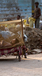"""New Delhi, India - July 15, 2012.  An Indian laborer sleeping under a mosquito net next to a garbage pile in the old part of the city. Dengue fever caused by mosquito bites is a seasonal, sometimes fatal viral disease transmitted by the Aedes mosquito, which bites during the day."""